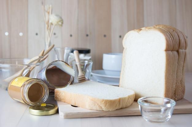 スライスの山チョッピングブロックに新鮮な香りのよいパン。コーヒーカップとキッチン用品は木製のテーブルの上に置きます。