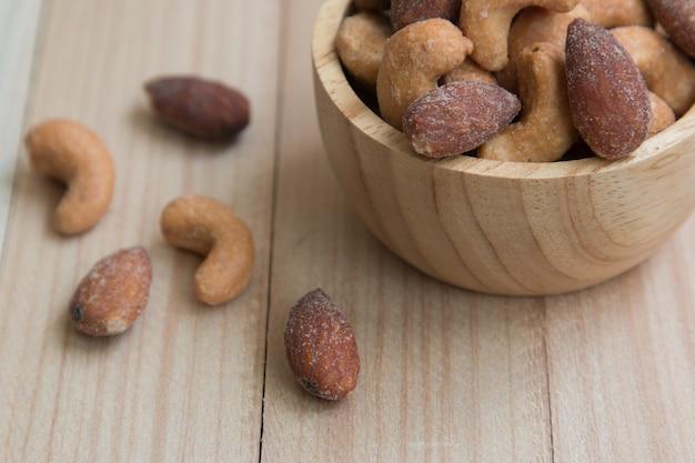 乾燥塩カシューナッツと木製のテーブル背景にボウルにアーモンド