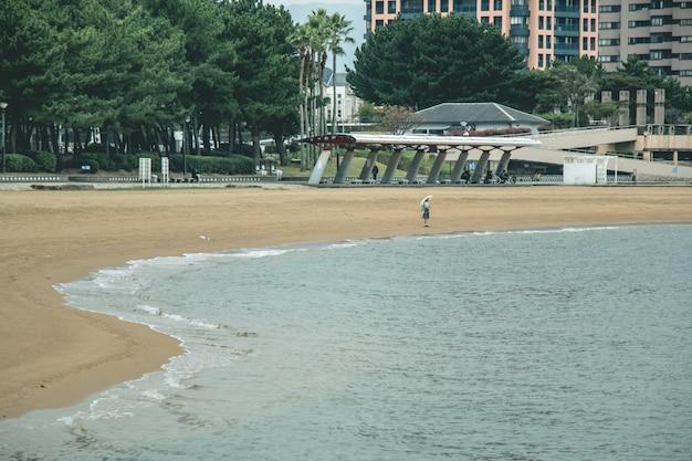 待っている傘を持つ少女と、ビーチの上に立つ