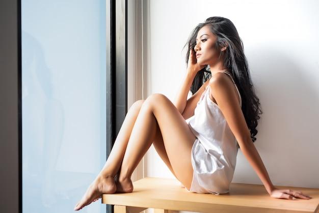 朝窓から見て座っている白い透明なガウンの女性。
