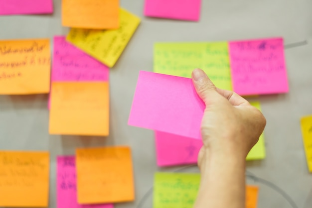 ブレーンストーミング戦略ワークショップのビジネスのために手書きメモを保持して手を閉じます。