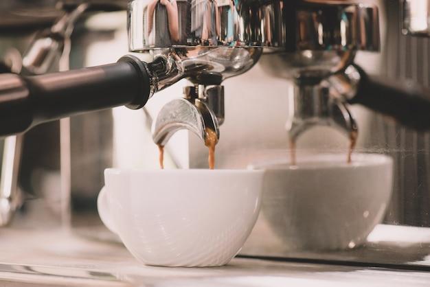 白いコーヒーカップとコーヒーマシンのコーヒーショップでのクローズアップ