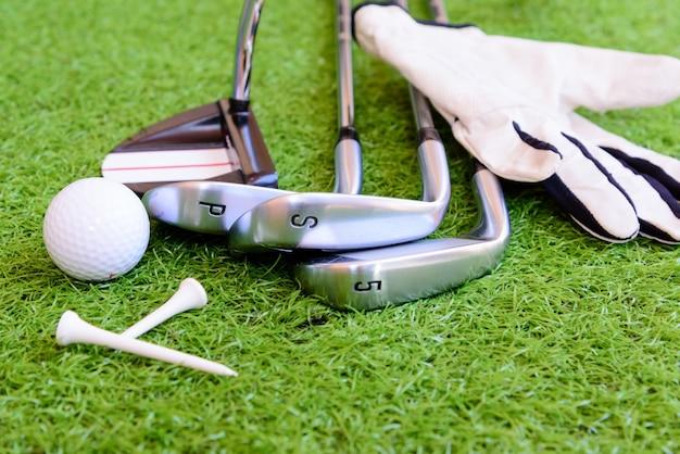 緑の芝生の背景にゴルフをするための機器。
