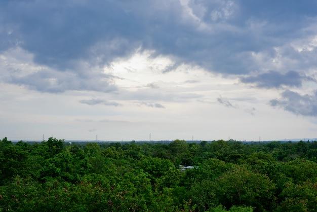 雨の降る前の暗い雨の雲の背景と田舎の緑の木の森