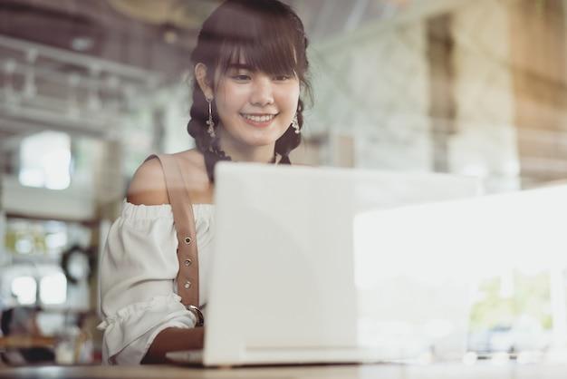 アジアの若い女性の笑顔とラップトップをコーヒーショップで使用