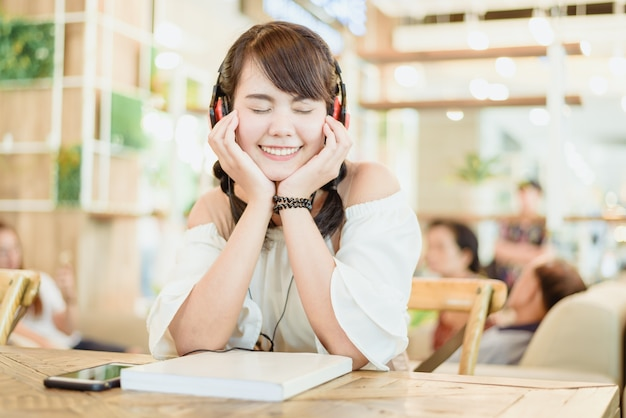 美しいアジアの若い女性の笑顔とヘッドフォンで聴く音楽の肖像画