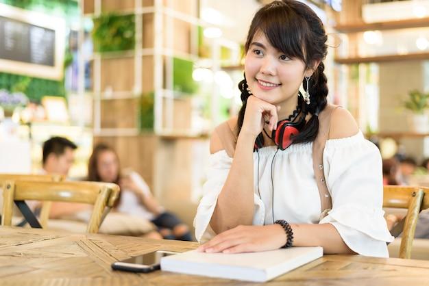 美しいアジアの若い女性の笑顔と幸せのヘッドホンの肖像