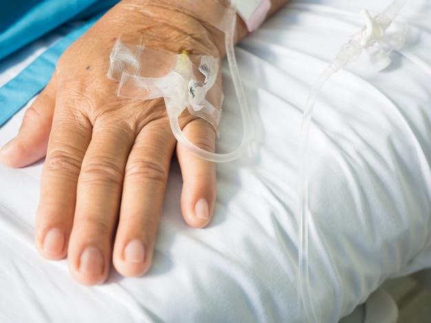 クローズアップの老婦人患者の手と静脈内点滴用生理食塩水ドリップセット白