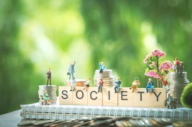 ミニチュアの人々、社会の言葉で木製のブロックに座っているビジネス人々のグループ。