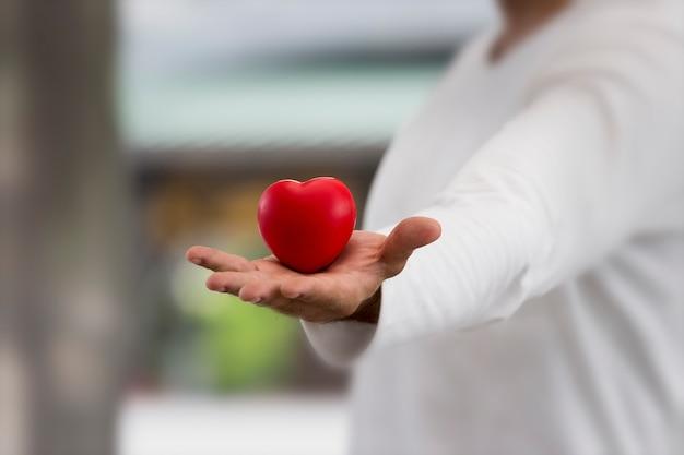愛する人に与えるために手に赤いハートのクローズアップは、誠実に愛を与える