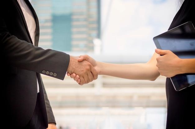 都市でオフィスビルの前に屋外で握手をしているビジネス人々。