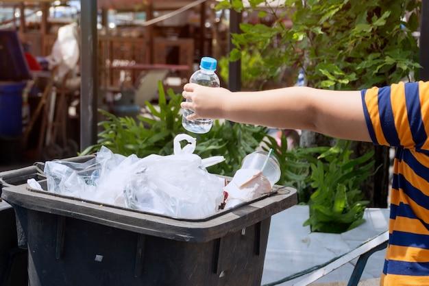 その少年は公園のゴミ箱にゴミを入れています。彼はボトルのゴミをゴミ箱に捨てる。