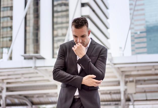 Бизнес-концепция разочарованный молодой человек в черном костюме стоит перед офисом.