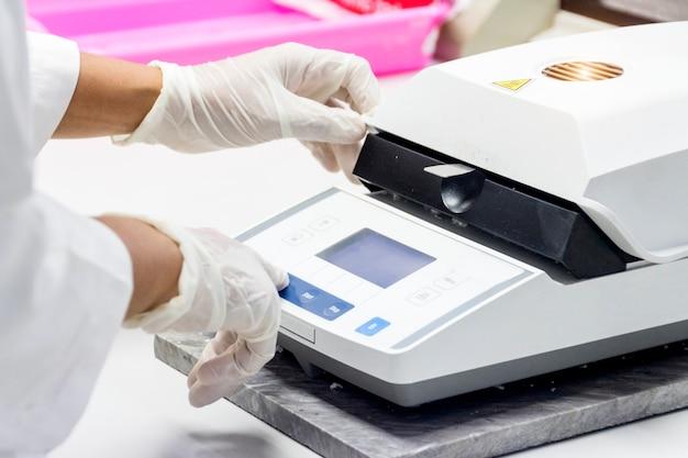 化学者は化学実験室で水分バランスによって水分を測定するためにサンプルをテストしています。