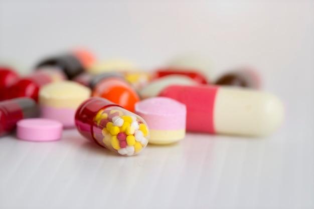 医学の概念カラフルな薬、カプセル、白い背景を持つ丸薬の写真を閉じた。