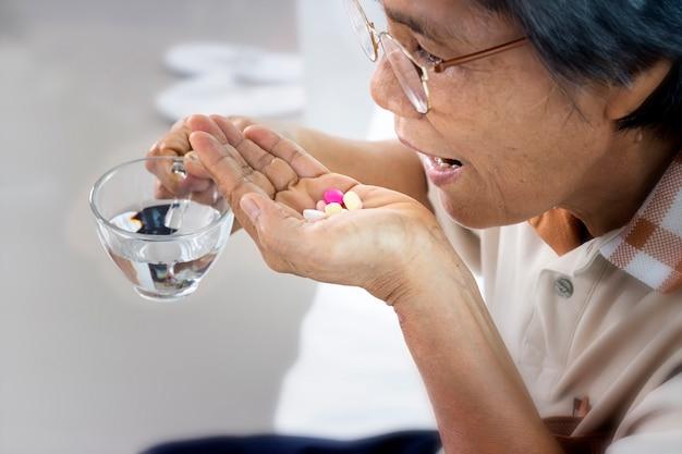薬と自宅で水のガラスを持つ年配の女性のクローズアップ