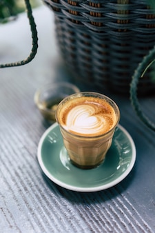 Кофейная чашка латте арт с зеленым блюдцем на фоне дерева