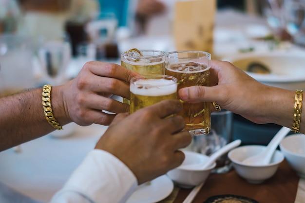 パーティーでのお祝いのためのビールのグラスを両手