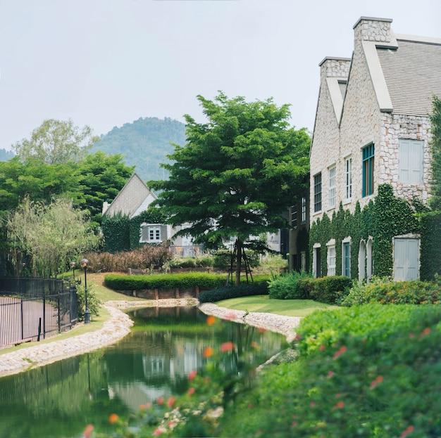 Красивое украшение английского кантри-стиля здания, покрытого зеленым растением