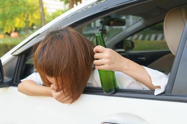 酔っているアジアの女性はあまり飲んでアルコールと運転中の車の後にめまいを感じる