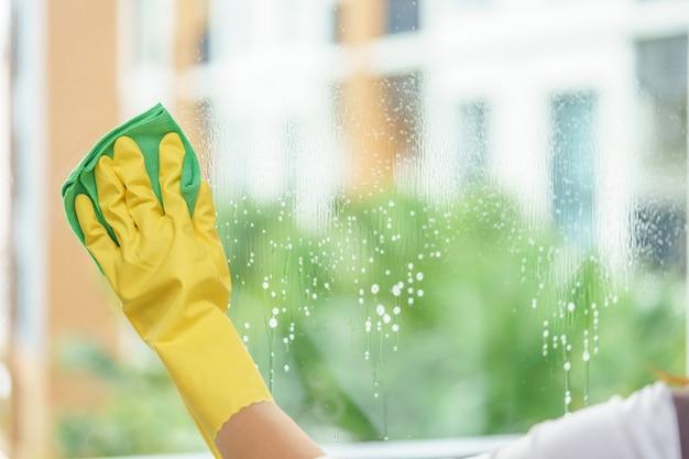 緑の布で鏡を清掃する女性の家政婦