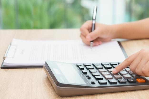 ローンのクレジットバランスを計算するために計算機を押す女性の手
