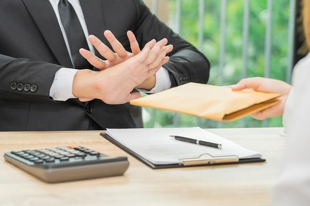 女性 - 腐敗の概念によって提供される封筒でお金を拒否するビジネスマン