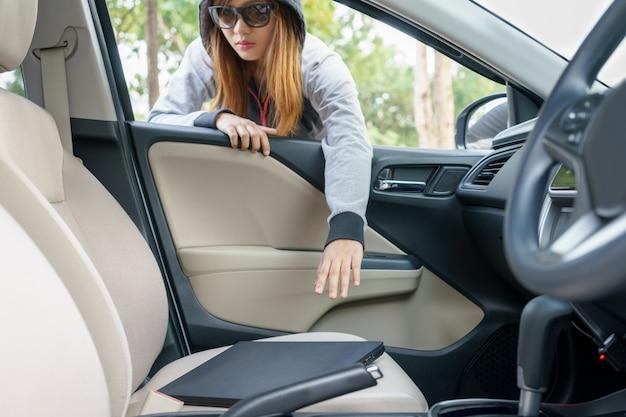女性の盗難は、車の盗難の概念の窓からラップトップを盗む。