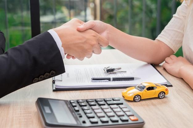 セールスマン、または自動車ローン契約締結後に女性と握手をする実業家