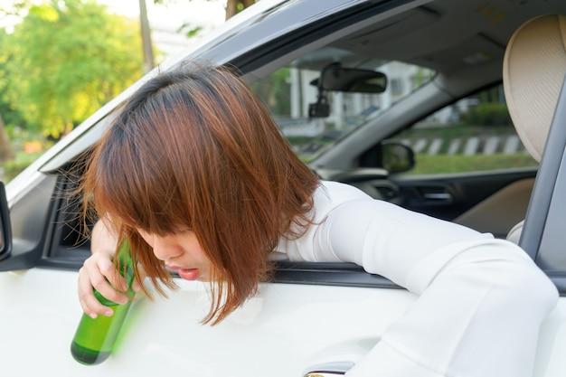酔っているアジアの女性は、あまりにも多くのアルコールと運転中の車を飲んだ後めまいを感じる。