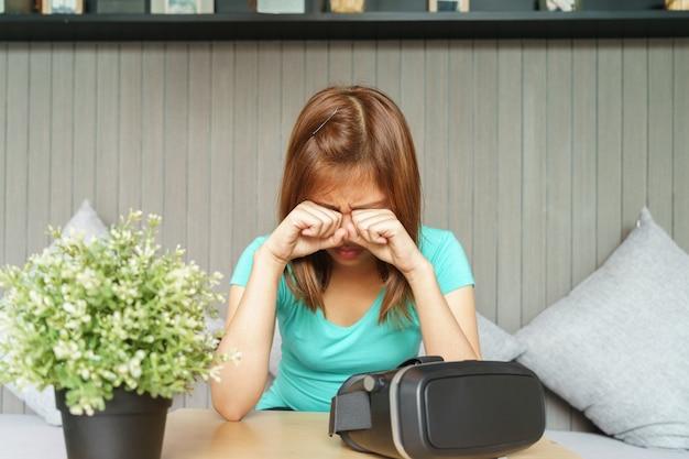 バーチャルリアリティーメガネを持つ若い女性が彼女の目を痛めます。彼女は目をこすっている。