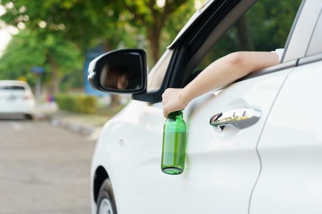 車の外で運転してビール瓶を持っている酔った女性