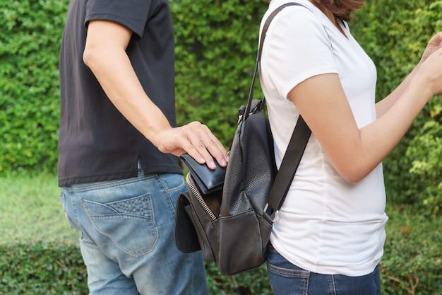 公園のバックパックで財布を盗もうとしている泥棒
