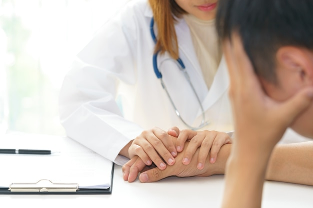 女性の手、明るいのために患者の手に触れる