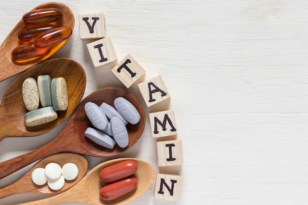 白い背景の上の木のスプーンでビタミン薬の様々な