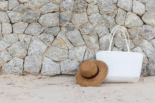 岩の壁が付いている浜の白い編まれた袋そしてパナマ帽子