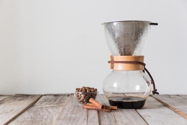 白の木製テーブルの上の豆とガラスの水差しと金属フィルターを使用して自家製のドリップコーヒー