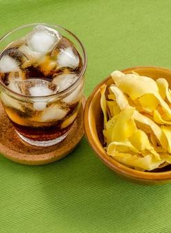 コーラとドリアンのチップは、緑色の背景で茶色の打撃でスナックフルーツを揚げ