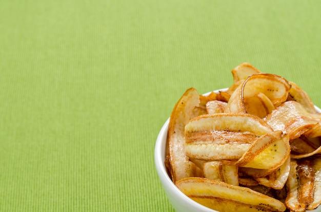 Сладкие банановые чипсы на зеленой скатерти