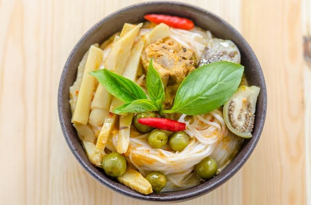 木製の背景に野菜とチキンカレーソースのライスヌードル