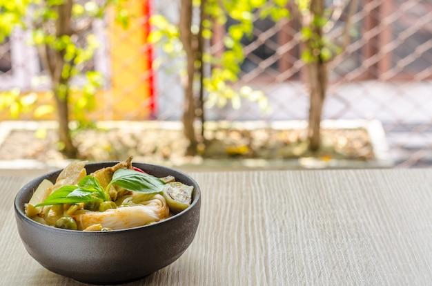 Рисовая лапша в курином соусе карри с овощами на деревянном фоне