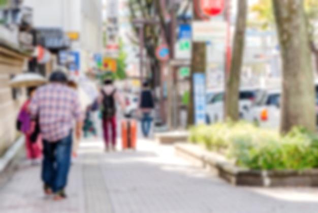 Затуманенное человек идет по улице города.