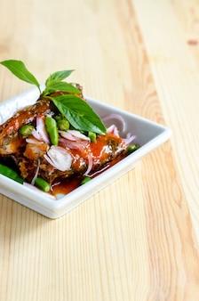 Острый салат из рыбных консервов сардины на деревянный стол