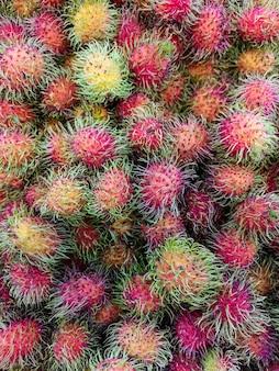 Свежие фрукты рамбутан для продажи на рынке. мягкий фокус.
