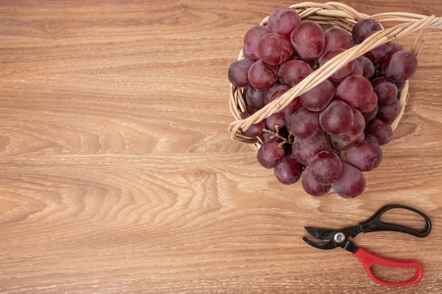 バスケットウッドの背景に新鮮なブドウ。テキストを追加するためのコピースペース。