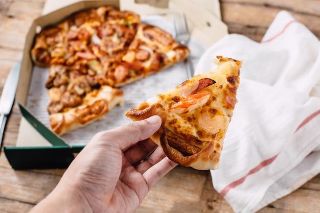 木製のテーブルの紙箱にピザ