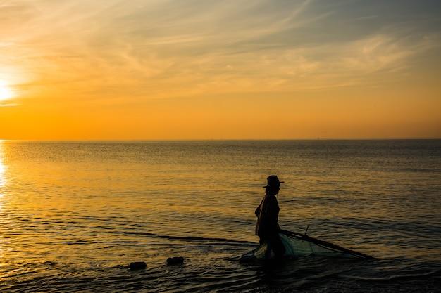 タイの日の出釣りや漁師のボートのシルエット