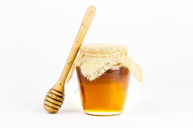 白い背景の上の木製の蜂蜜ディッパー