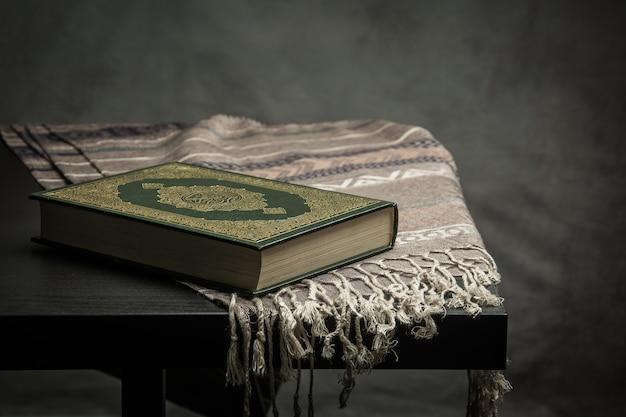 コーラン - テーブルの上のイスラム教徒(すべてのイスラム教徒の公用品)の聖典、静物