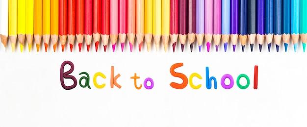 Вид сверху баннерного сообщения «снова в школу» с цветным карандашом предметы для школы на белом фоне